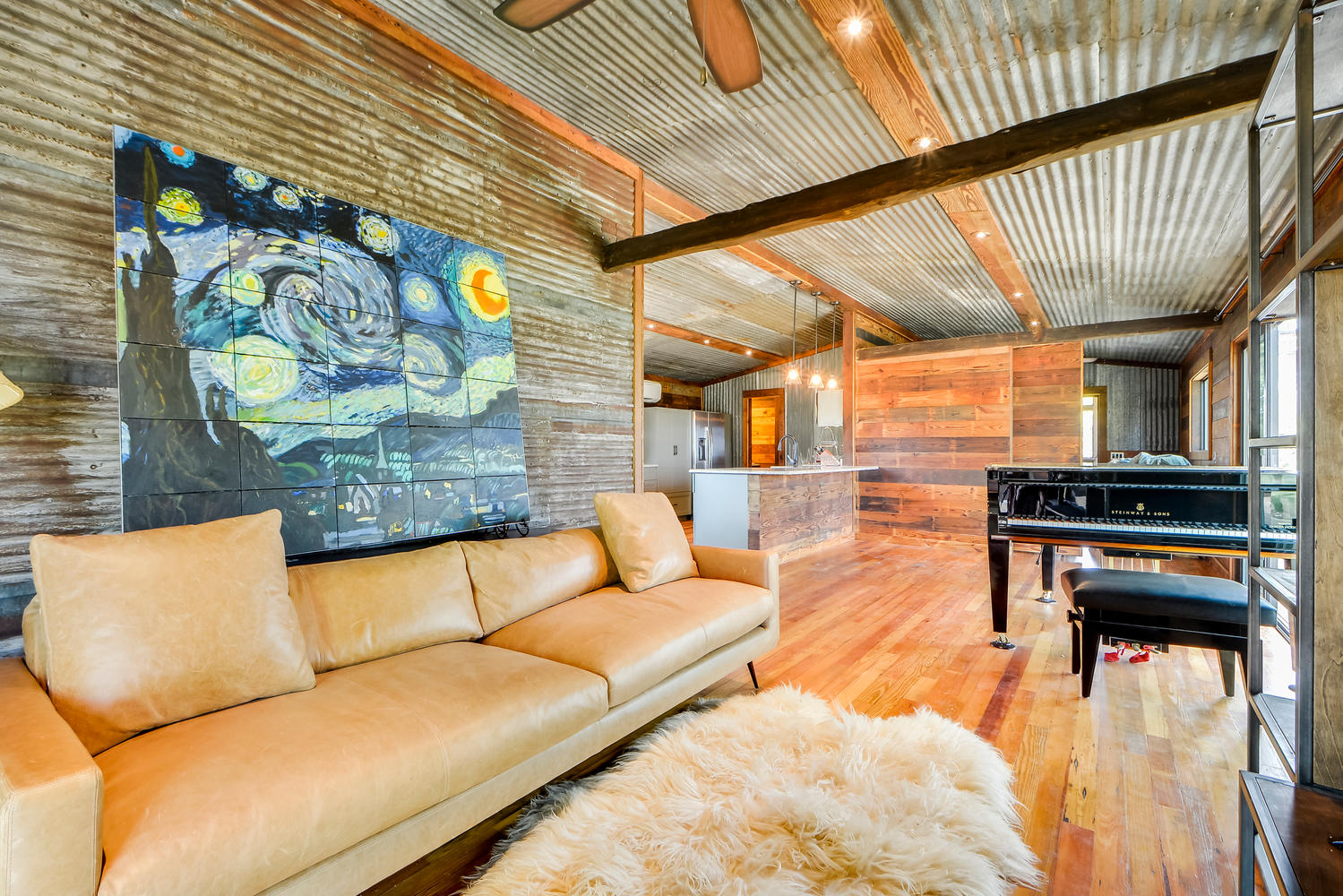 Interior of a small modular home by Reclaimed Space with a baby grand piano and seven foot sofa.