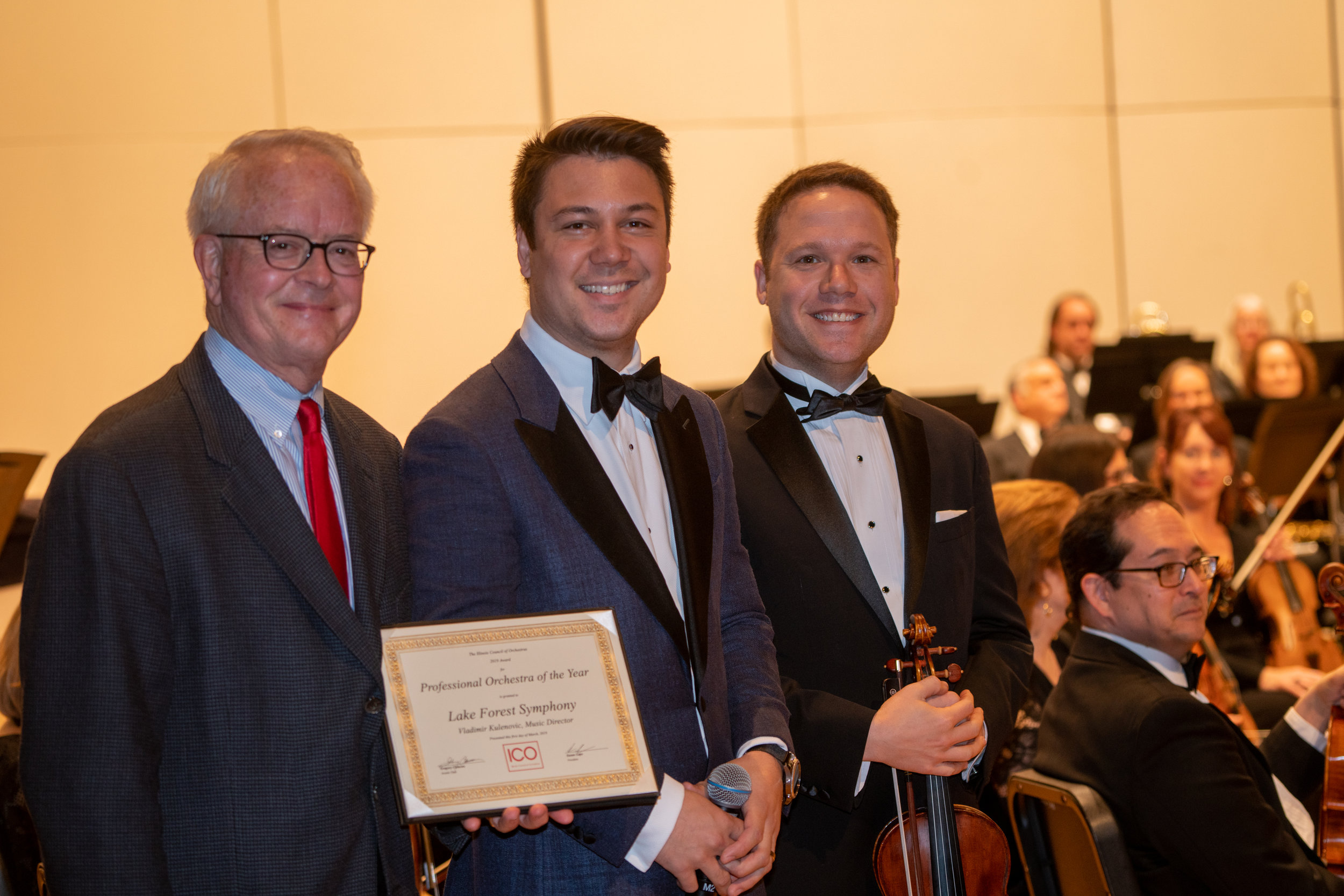 Executive Director Tim Corpus and Concertmaster Netanel Draiblate accept the award for Orchestra of the Year from Tom Sharp and the Illinois Council of Orchestras