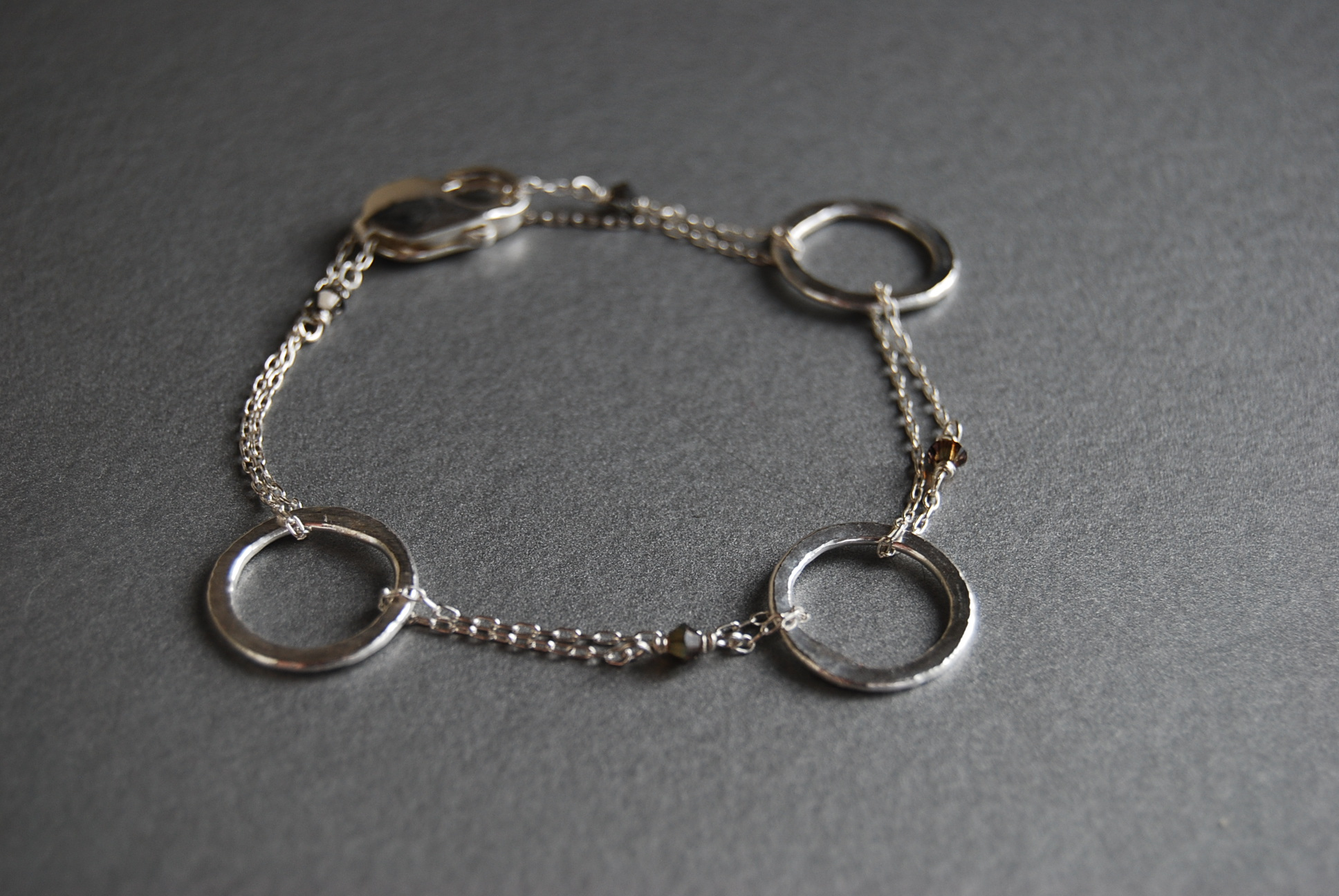 Fine Silver Ring Bracelet :  Fine silver rings are hand made and hammered.  They are linked along with sterling silver chain and Swarovski crystals.
