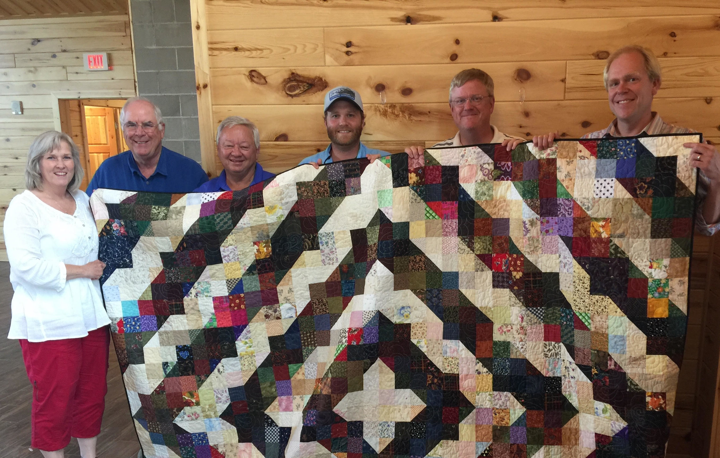 """VLM received this wonderful quilt from the """"Going to Pieces Quilting Group"""".    Pictured here are VLM board members Sheila Davidson (Virginia), Tom Whittaker (Duluth), Keith Eggert (Hibbing), Mike Olson (Grand Rapids), Joel Abenth (VLM Executive Director), and Andy Mork (St Paul)."""