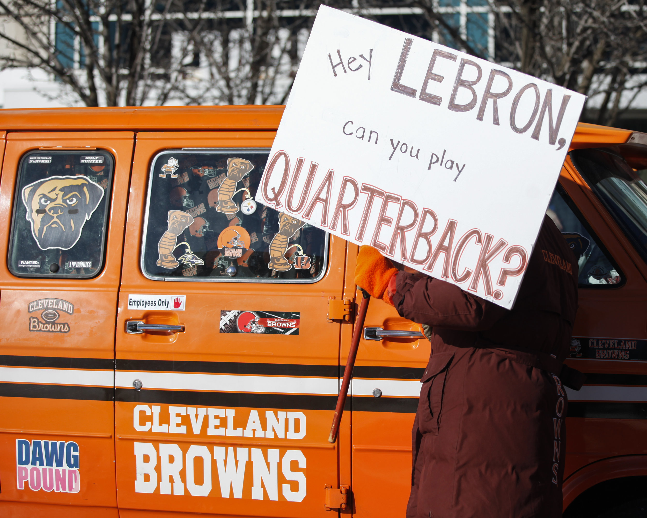 "A Cleveland Browns fan holds up a homemade sign, ""Hey Lebron, can you play quarterback?"" during the Browns 0-16 parade."