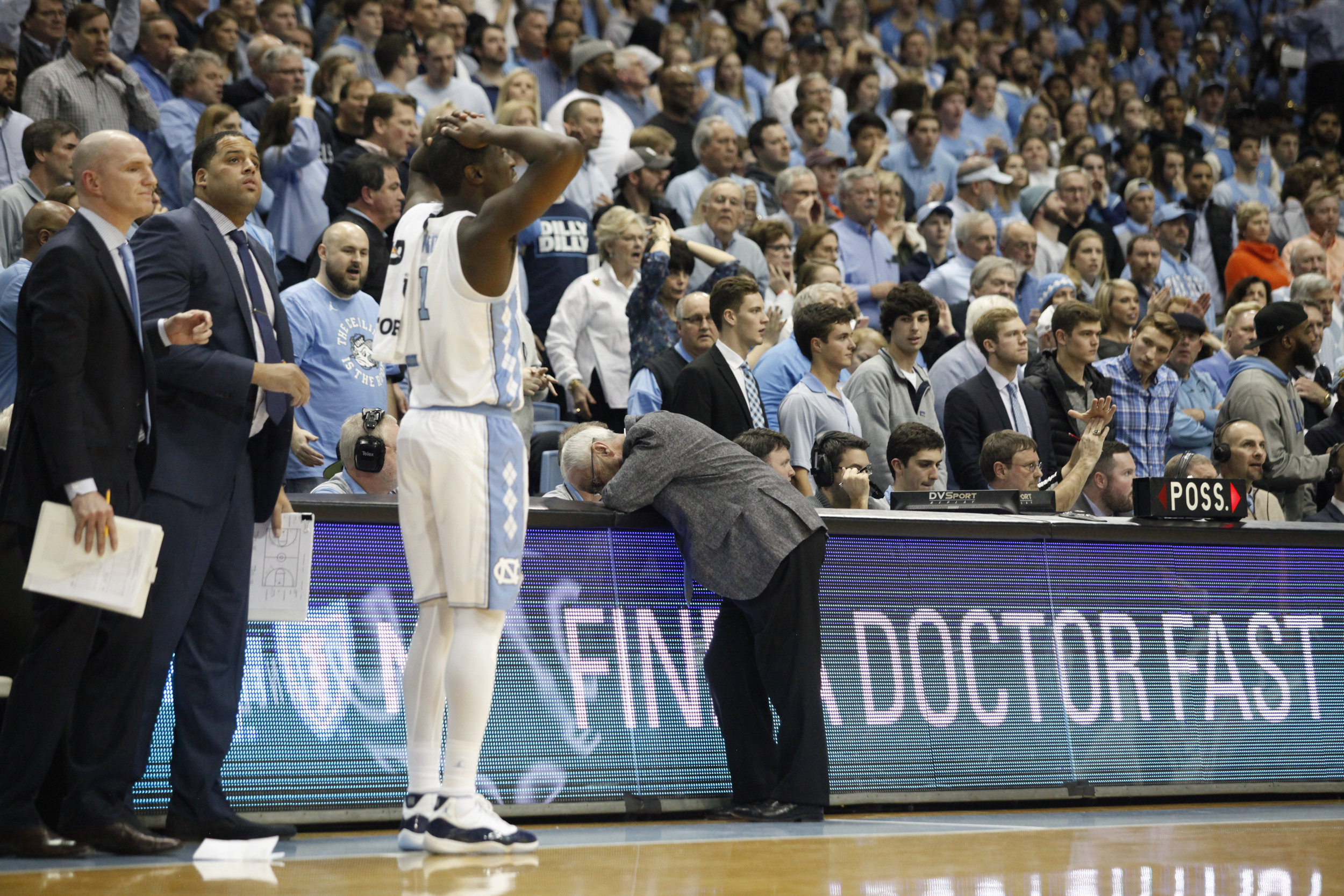 """North Carolina coach Roy Williams leans on a table reading """"Find A Doctor Fast"""" during the game against N.C. State at the Dean Smith Center."""