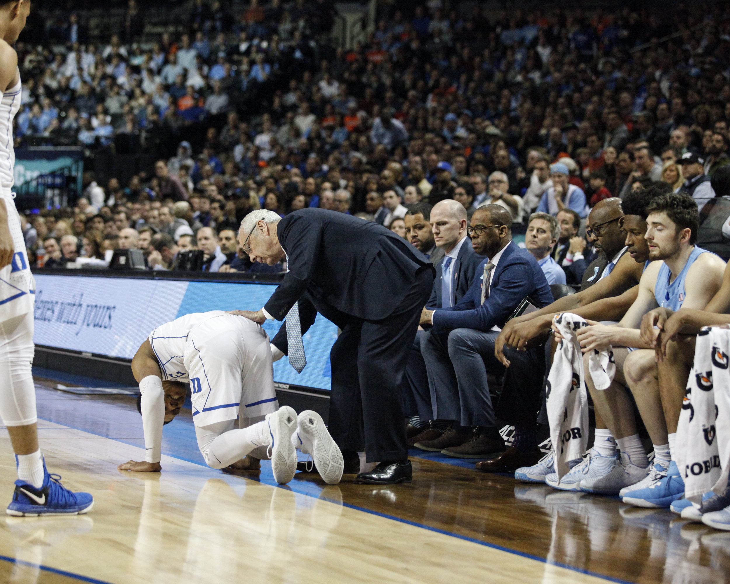 UNC head coach Roy Williams leans down to help Duke's Tre Duval with an injury during the ACC Tournament game at the Barclay Center in Brooklyn, New York.