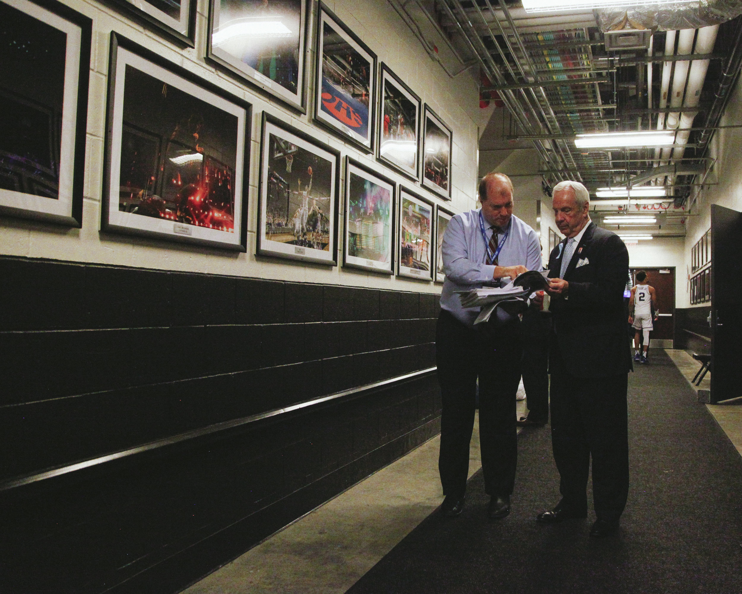 Roy Williams and UNC SID Steve Kirschner meet in the hallway after UNC beat Miami in the ACC Tournament at the Barclay Center in Brooklyn, New York.