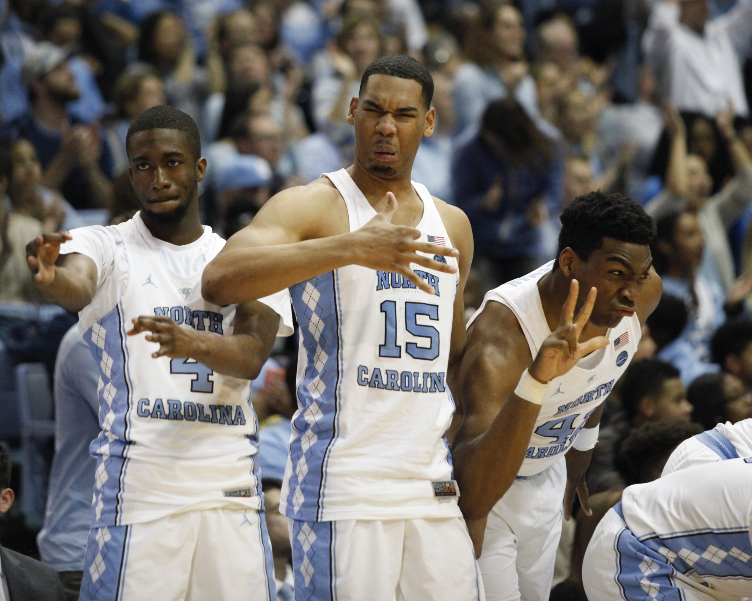 UNC basketball players Brandon Robinson, Garrison Brooks, and Brandon Huffman hold up three fingers after Kenny Williams knocks down a three point shot.