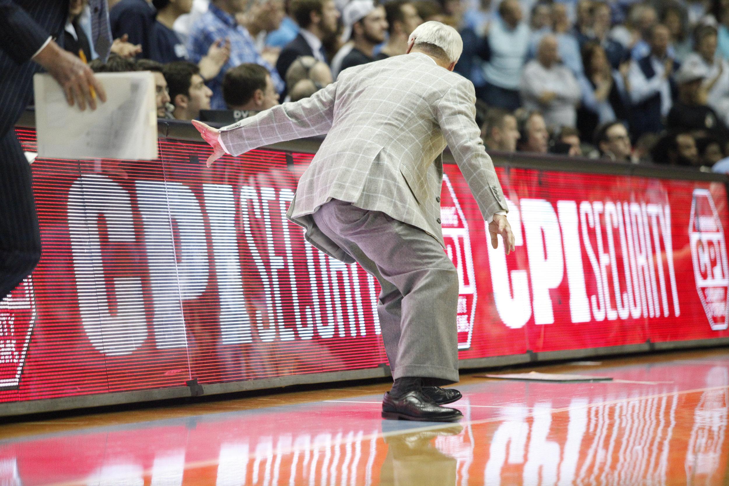 UNC head coach Roy Williams reaches back to catch himself as he has a vertigo attack during a game at the Dean Smith Center.