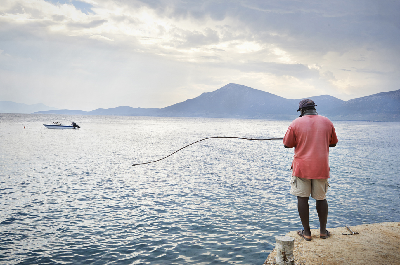 Ernest, the Island's caretaker fishing with a homemade rod. fisherman fishing photography photographer boat london greece retreat sunset pink shirt mountains sea jetty still life african