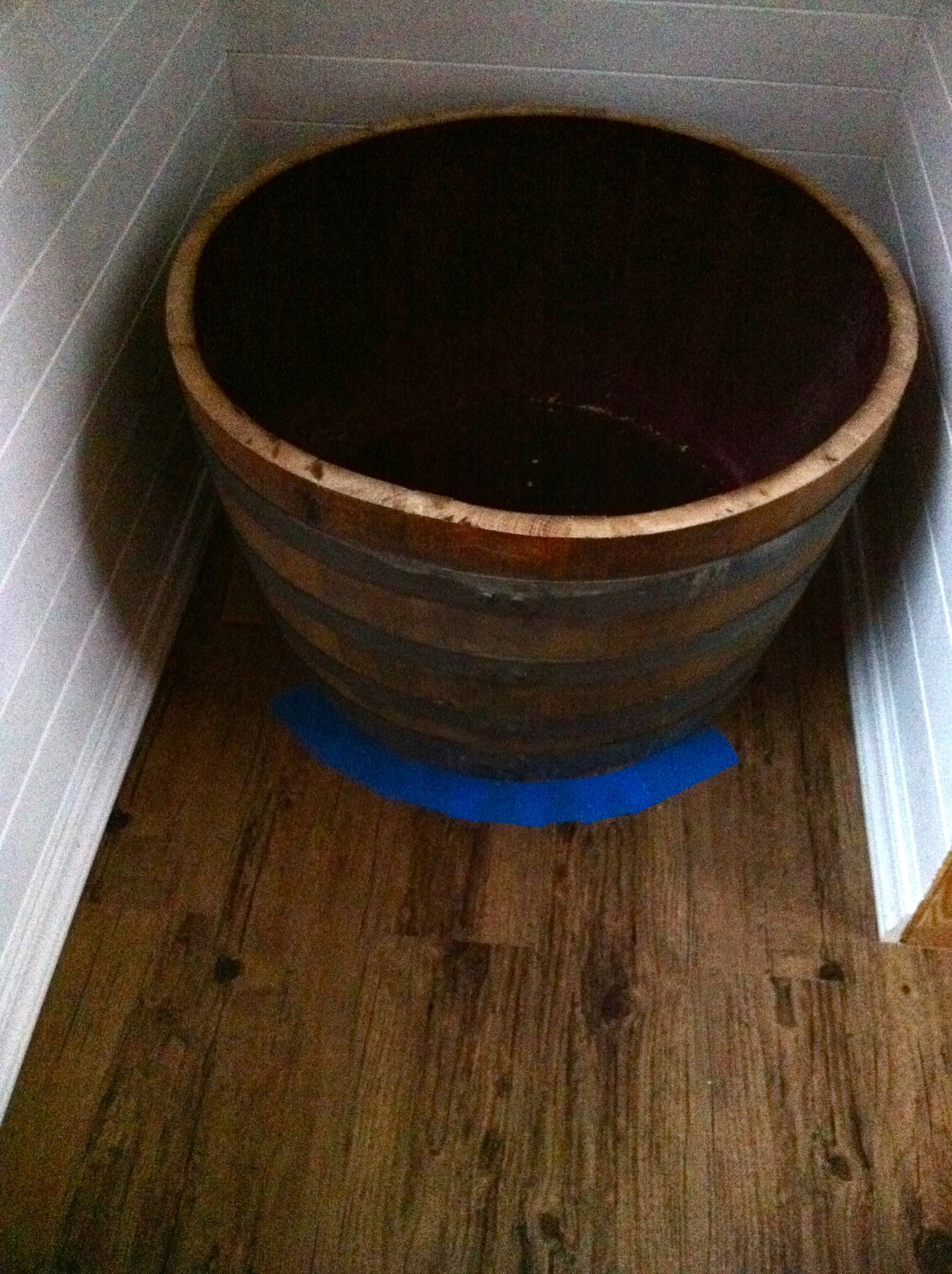 Our half cut wine barrel will be used as the water basin of the shower. Getting it into place for the shower drain.