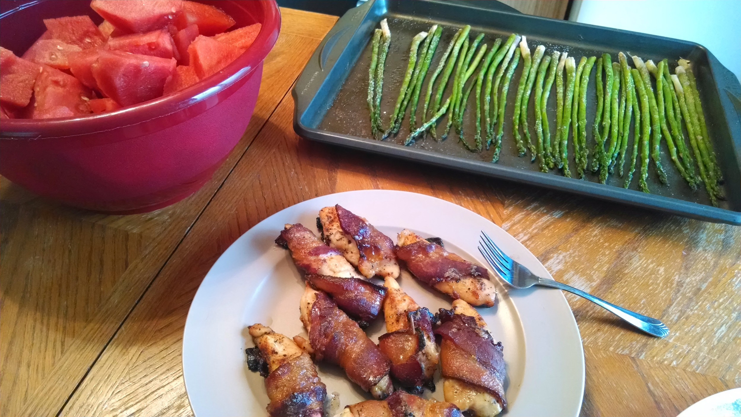Bacon-wrapped chicken, baked garlic asparagus, and some watermelon