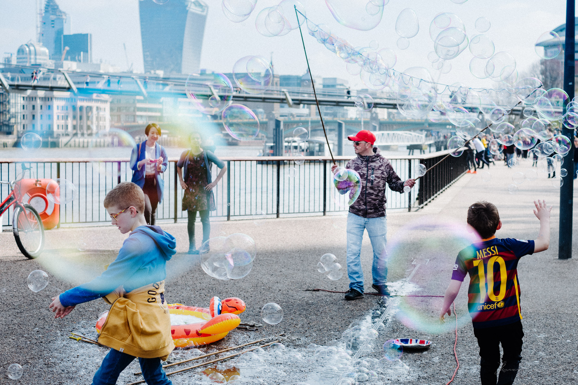 Man making bubbles and Kids playing on London's Southbank