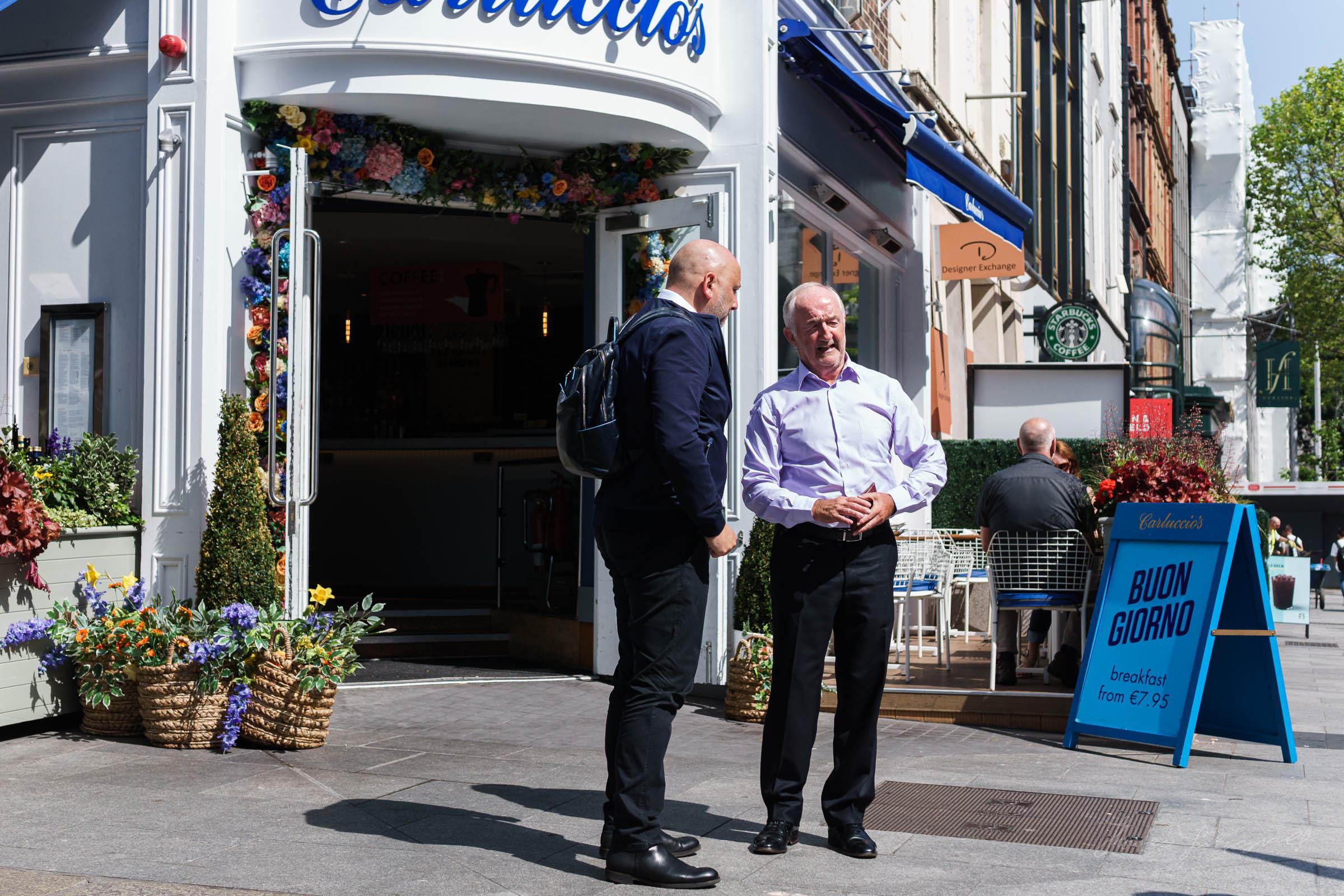 Two men talking outside Carluccios in Dublin