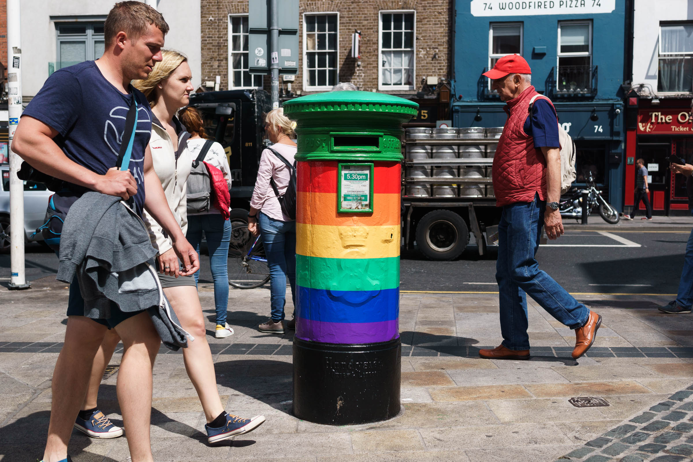 People walking in front of multicoloured post box