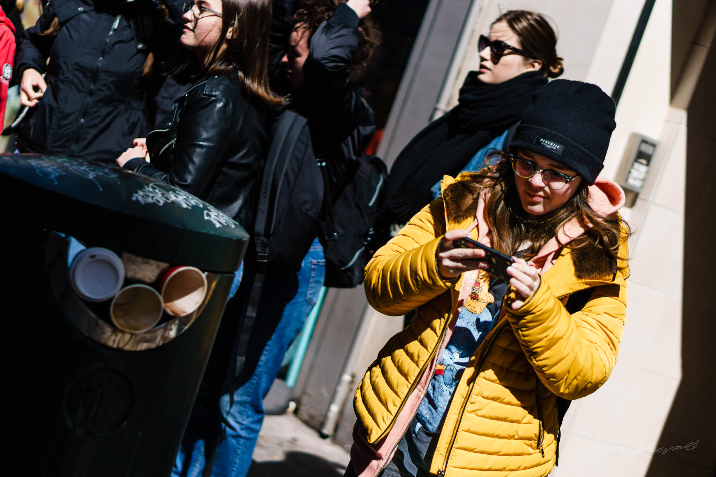 Woman looking at photos on her phone - Street Photography in Dub