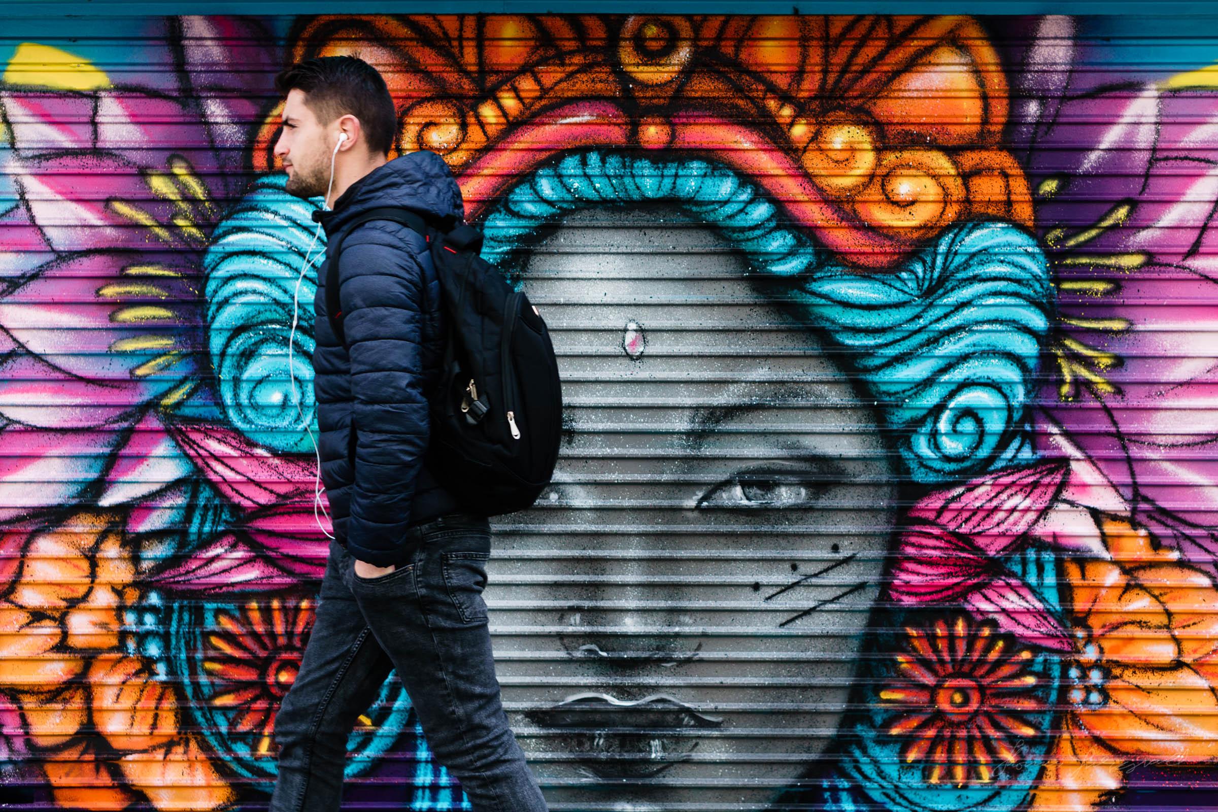guy walking past multicoloured shutters