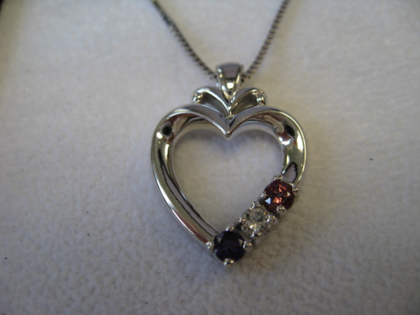 This is an example of a piece we made for a Mother's Day gift in 14k white gold.  It is set with genuine amethyst, diamond and rhodolite garnet.