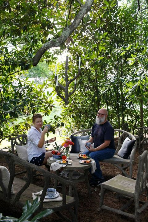 Thea and Cecil pretend to enjoy having tea in a setting under a magnolia tree.