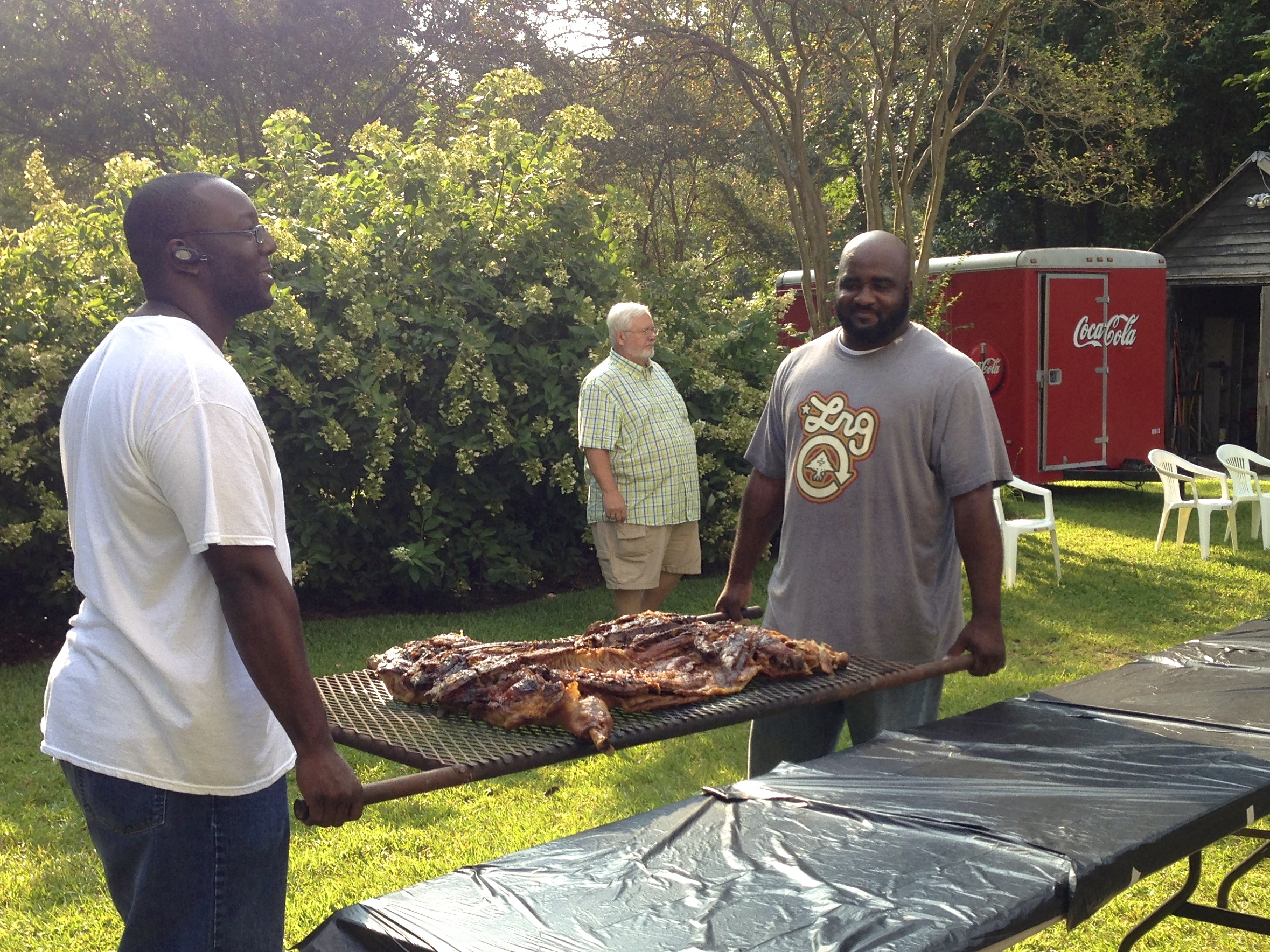 """""""Men On A Mission"""" bring in the first of the two barbecued whole pigs."""