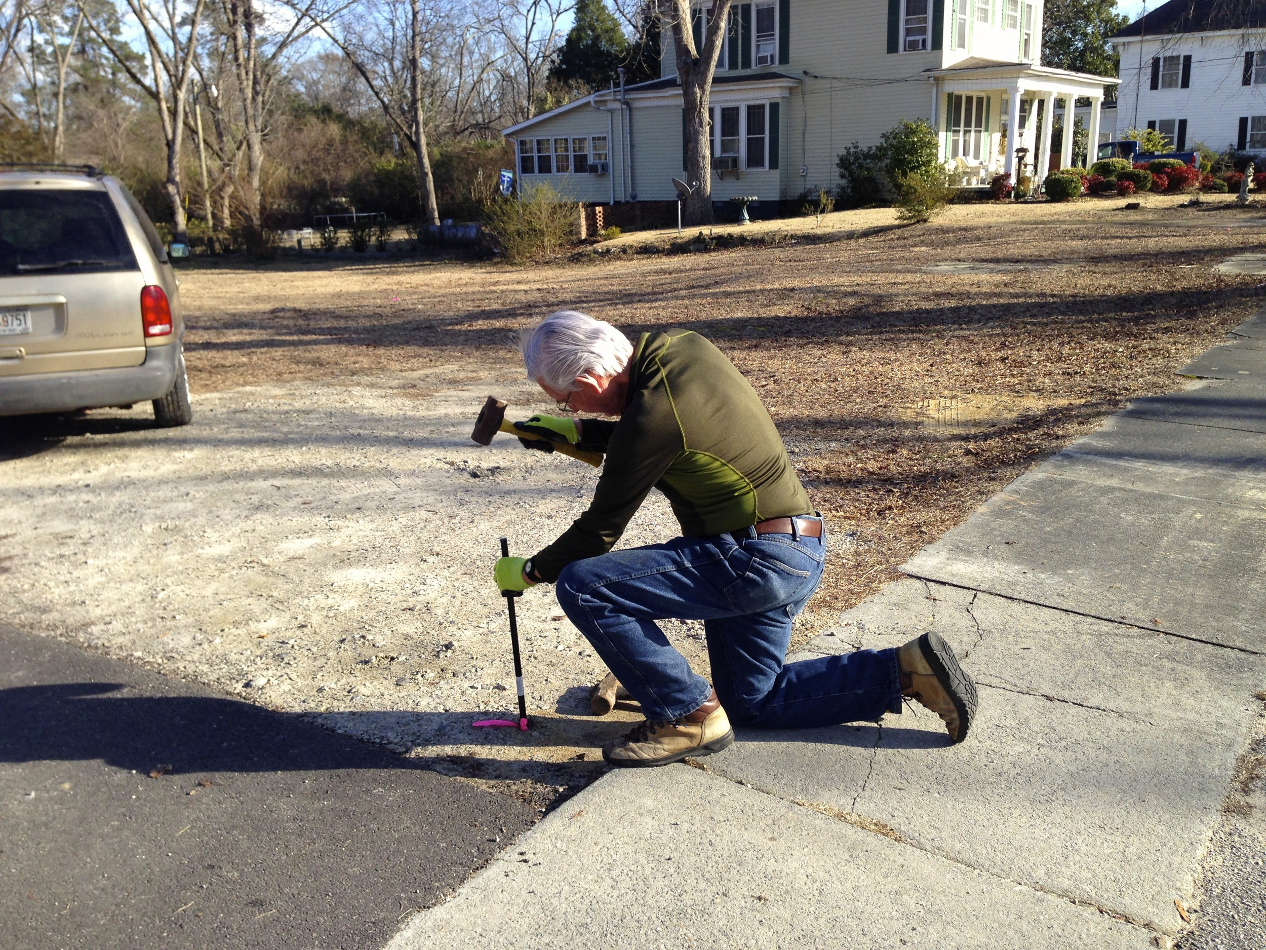 Robert hammers in the surveyor's marker at the top of the east lot.