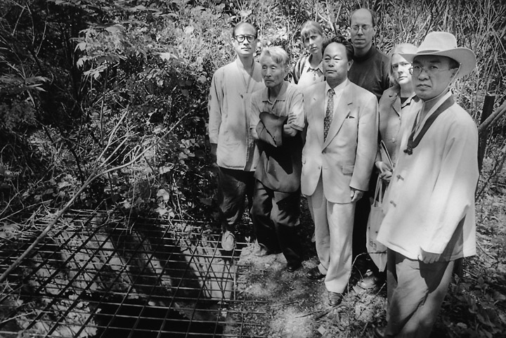 A Korea Truth Commission research delegation at a massacre site in the mountains.