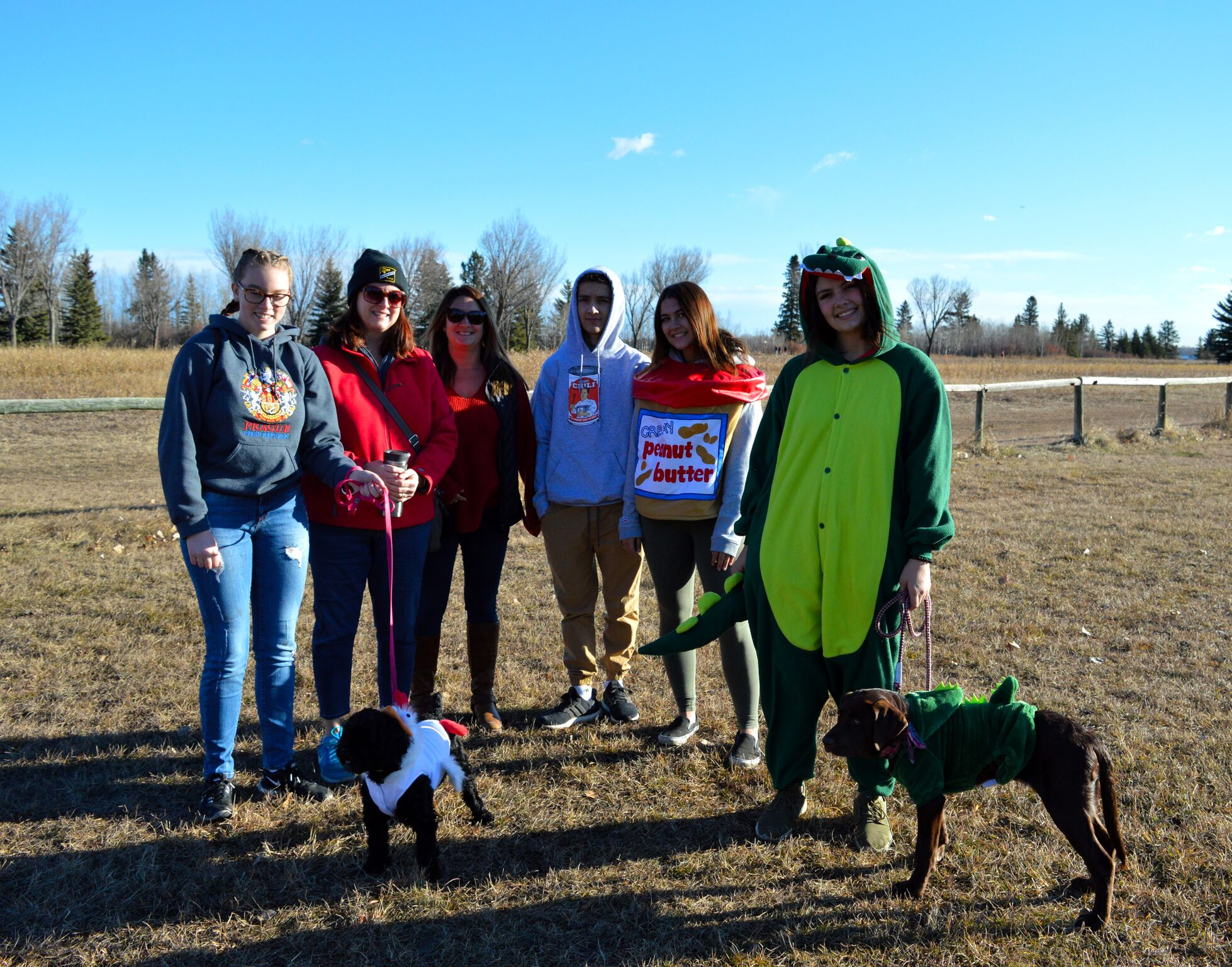 First place prize winners: matching dinosaurs, posing with friends at 2018 Tails of Help Howloween Dog walk