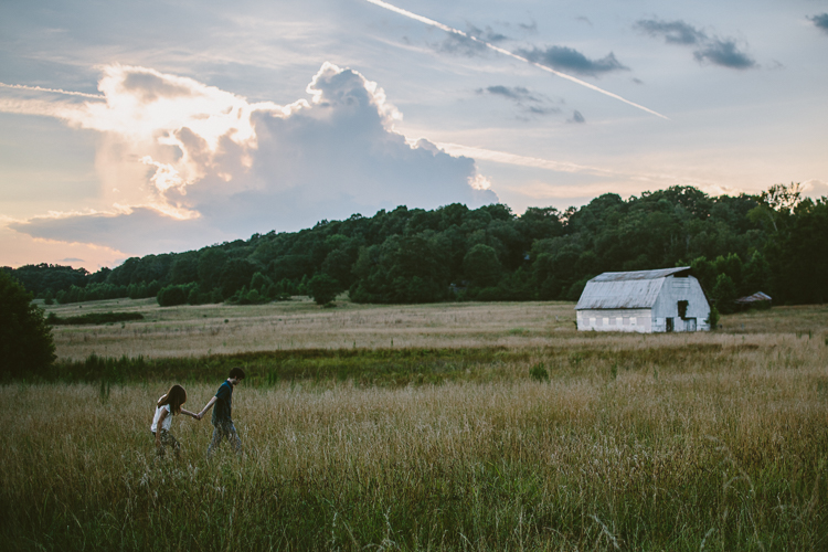 Couple Walking Through the Field with a Barn