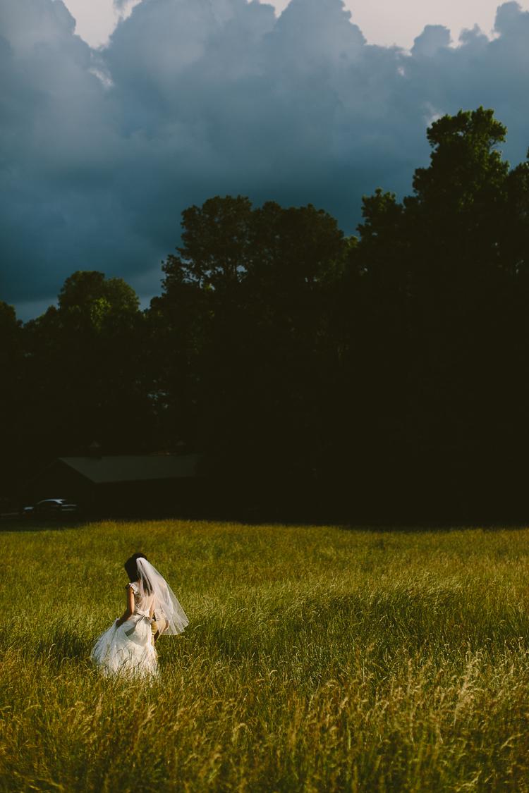 Bride and Groom Walking Through Field