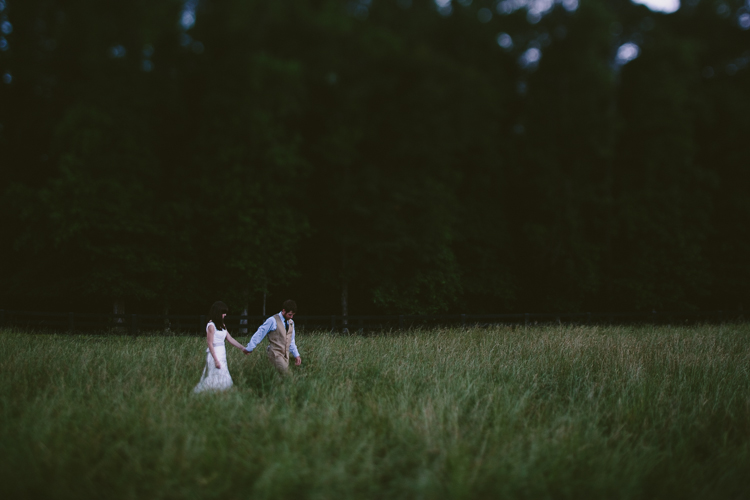 Bride and Groom Holding Hands Walking Through the Field