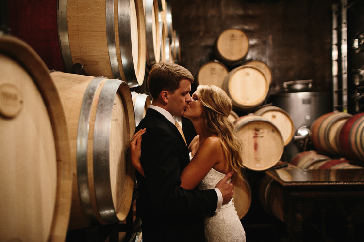 The Bride and Groom Sharing a Sweet Kiss in the Wine Cellars