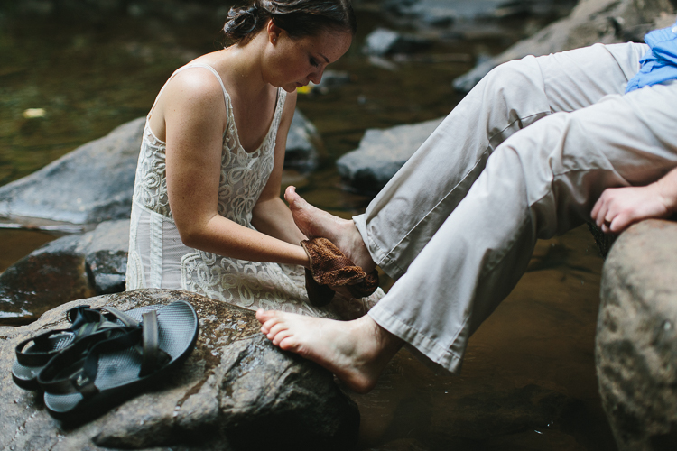 Bride washing groom's feet during wedding ceremony