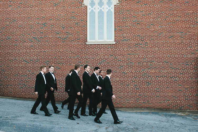 groom and groomsmen walking down the street together
