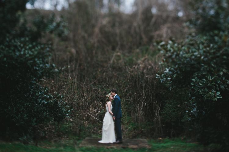 groom kisses his bride's forehead