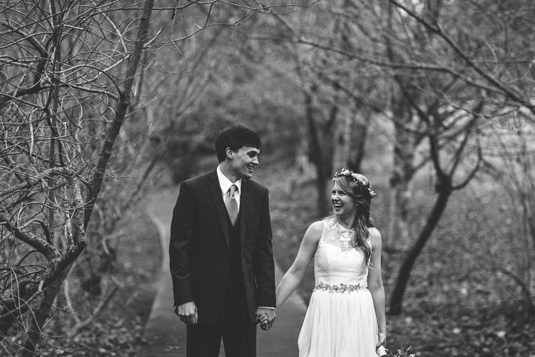 bride and groom walking down sidewalk holding hands
