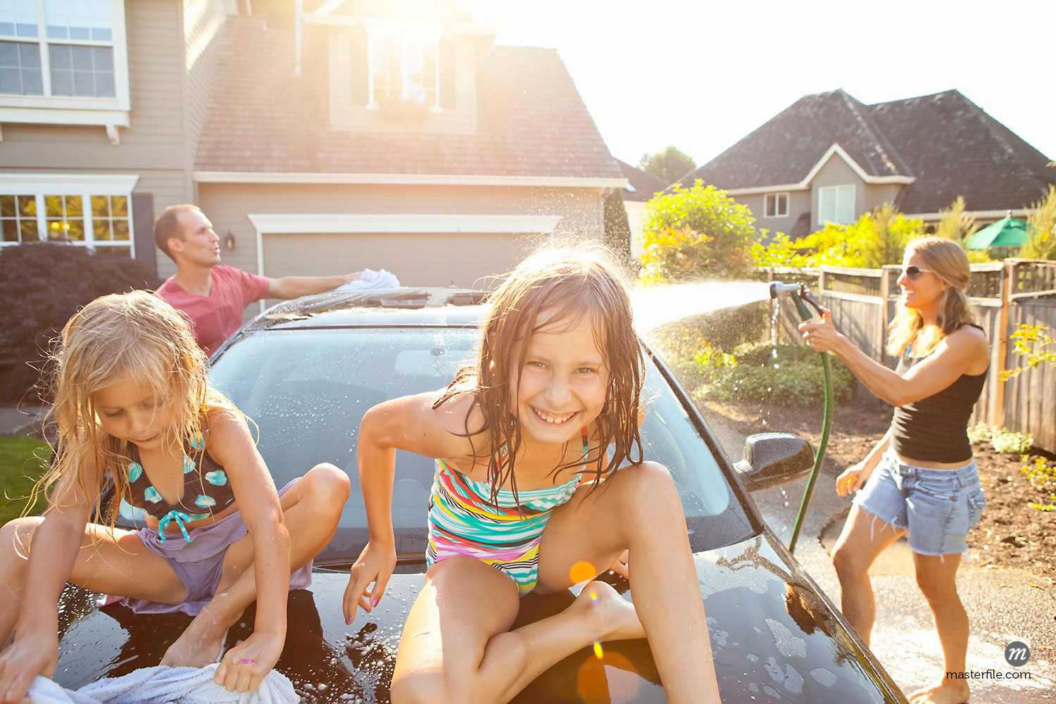 Family washing their car in the driveway on a sunny summer afternoon in Portland, Oregon, USA  ©  Ty Milford / Masterfile