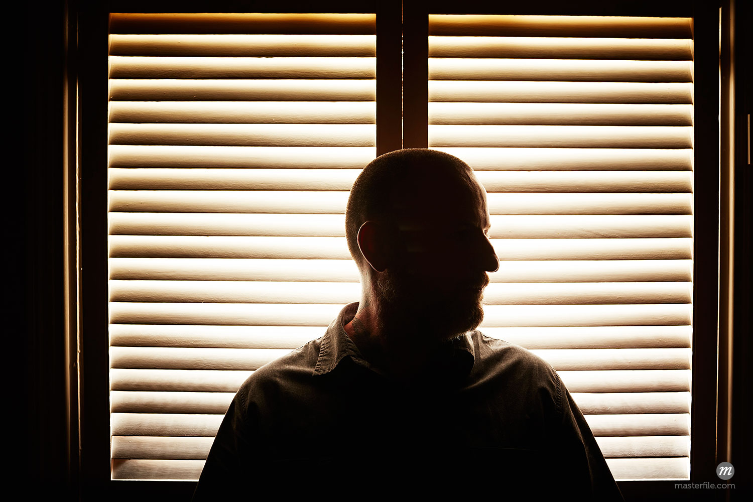 Portrait of silhouetted mature man in front of window blind  ©  Cultura RM / Masterfile