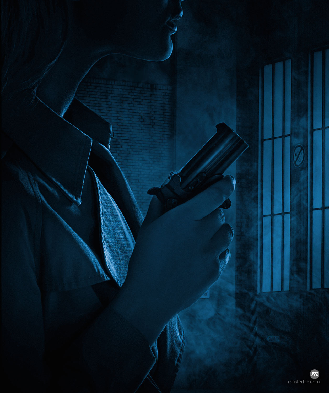 Silhouette of woman holding gun in dark room  © Masterfile