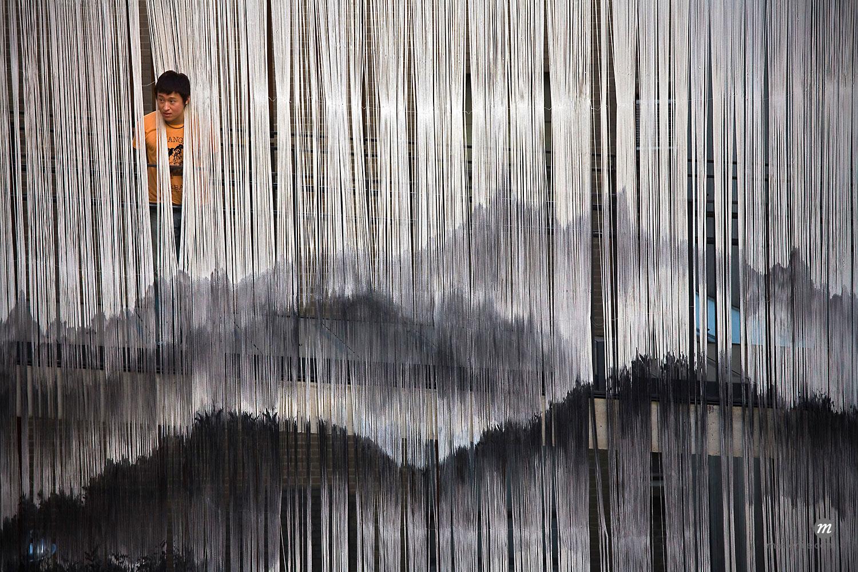 Man Looking through Hanging Tassels, Insadong, Seoul, South Korea  ©  R. Ian Lloyd / Masterfile