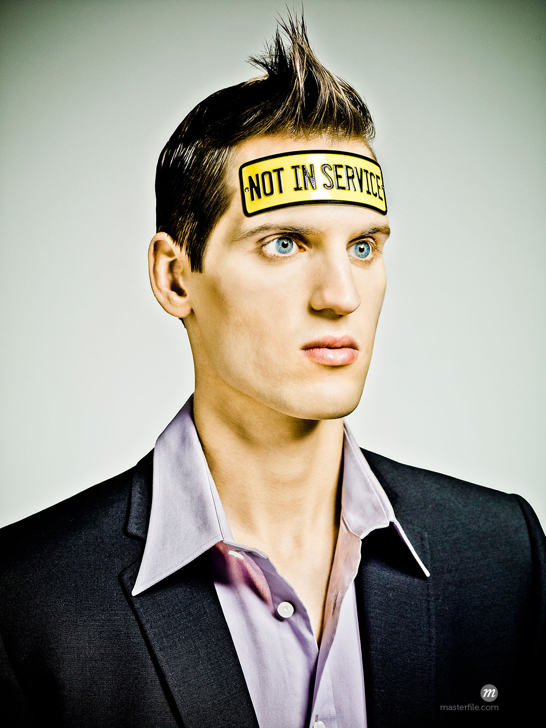 """Male fashion model looking """"vacant"""" with a tin plate bolted to his head saying """"Not In Service""""  ©  Dana Hursey / Masterfile"""