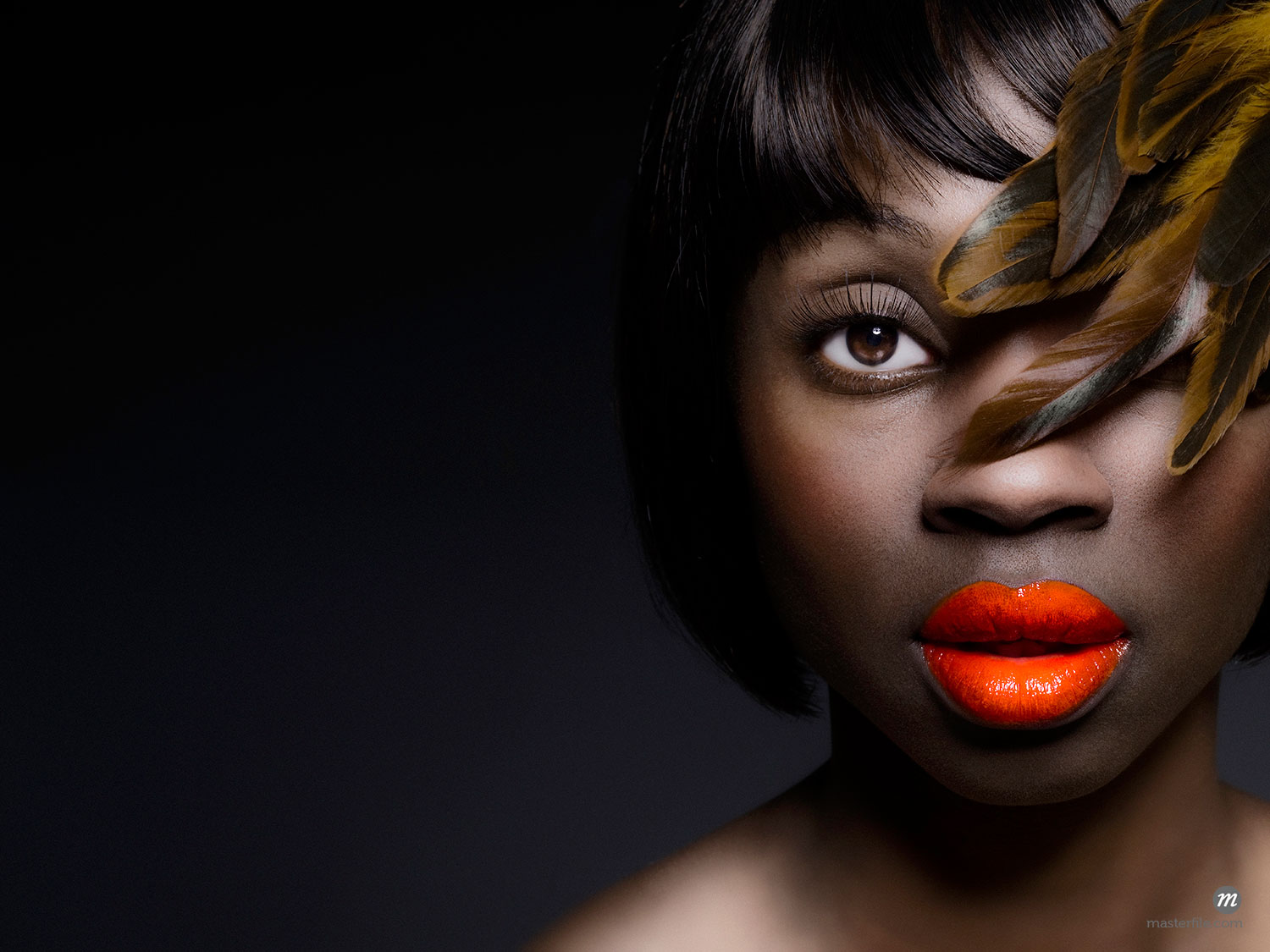 Close-up portrait of a glamorous model with feathers covering one eye and vibrant lipstick  ©  Dana Hursey / Masterfile