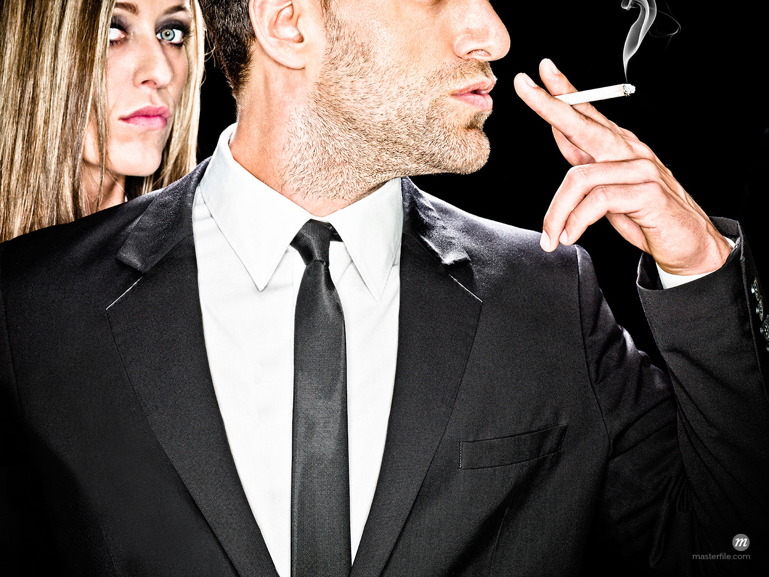 Close-up of man in black suit against a black background smoking a cigarette, with head of serious blonde woman looking over shoulder  ©  Dana Hursey / Masterfile