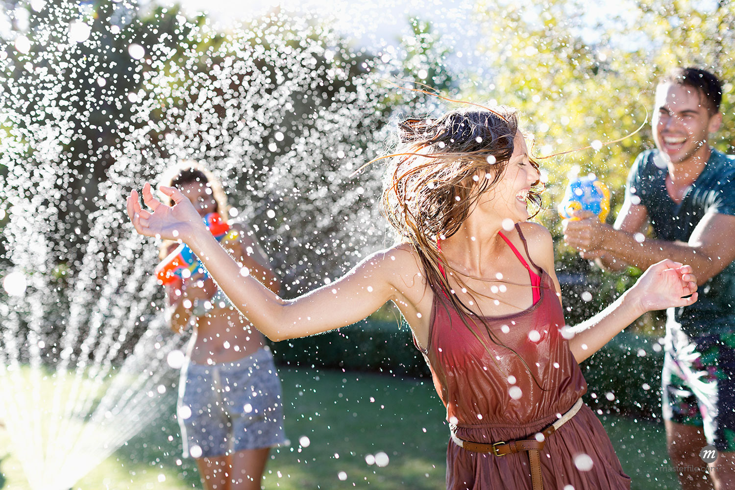 Friends playing with water guns in sprinkler  © Masterfile Royalty-Free
