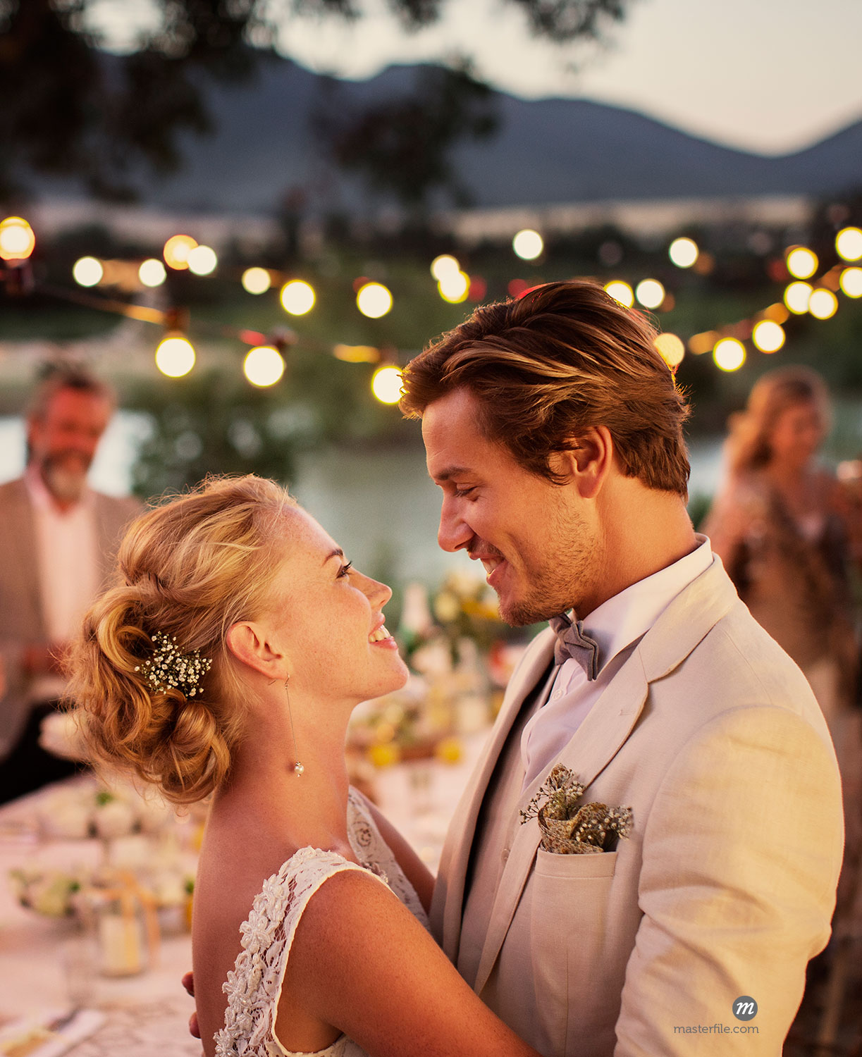 Portrait of young couple dancing in garden during wedding reception  © Caia Image / Masterfile