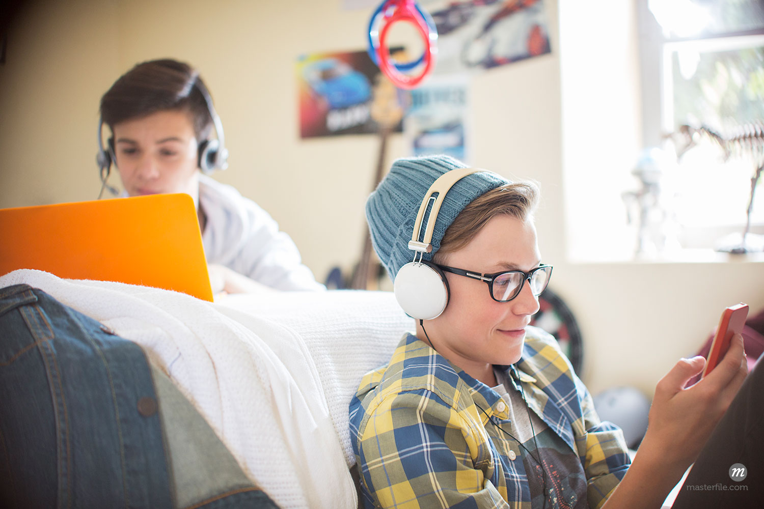 Two teenage boys using electronic devices in room  © Caia Image / Masterfile
