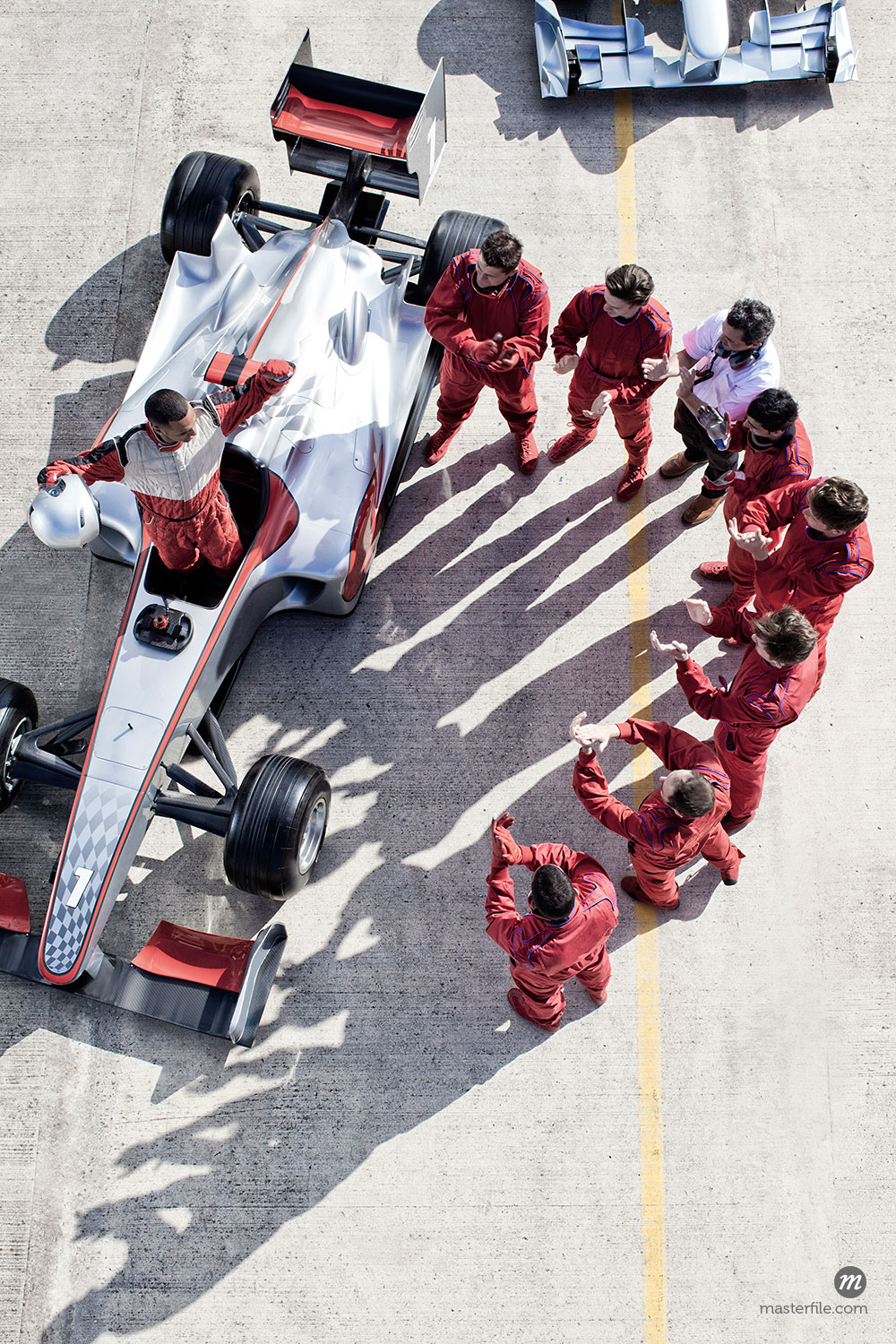 Racing team surrounding driver and caron track  © Caia Image / Masterfile