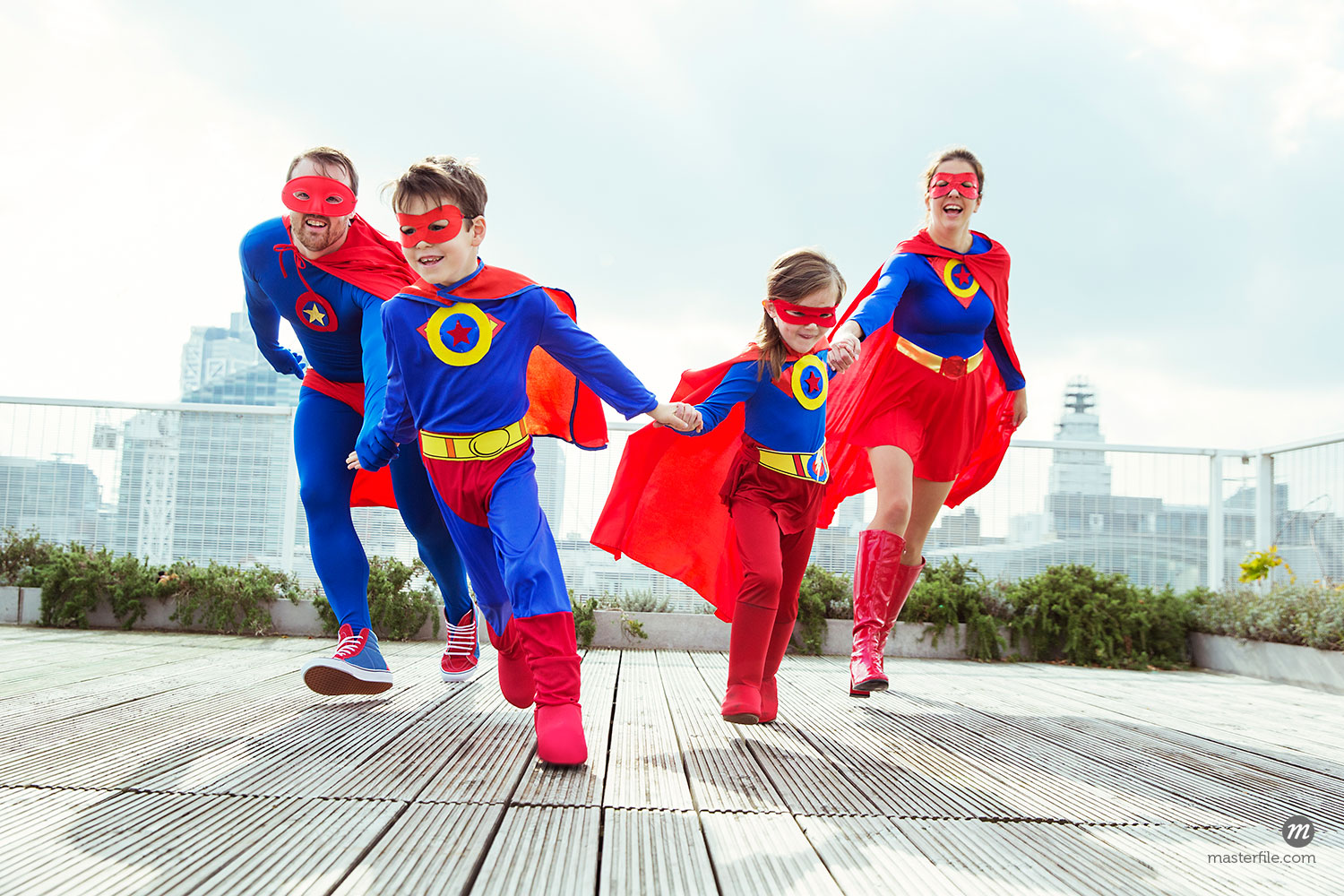 Superhero family playing on city rooftop  © Caia Image / Masterfile