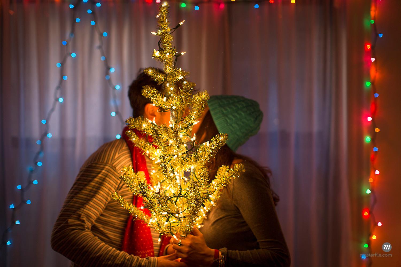 Young couple kissing behind illuminated Christmas tree  © Masterfile