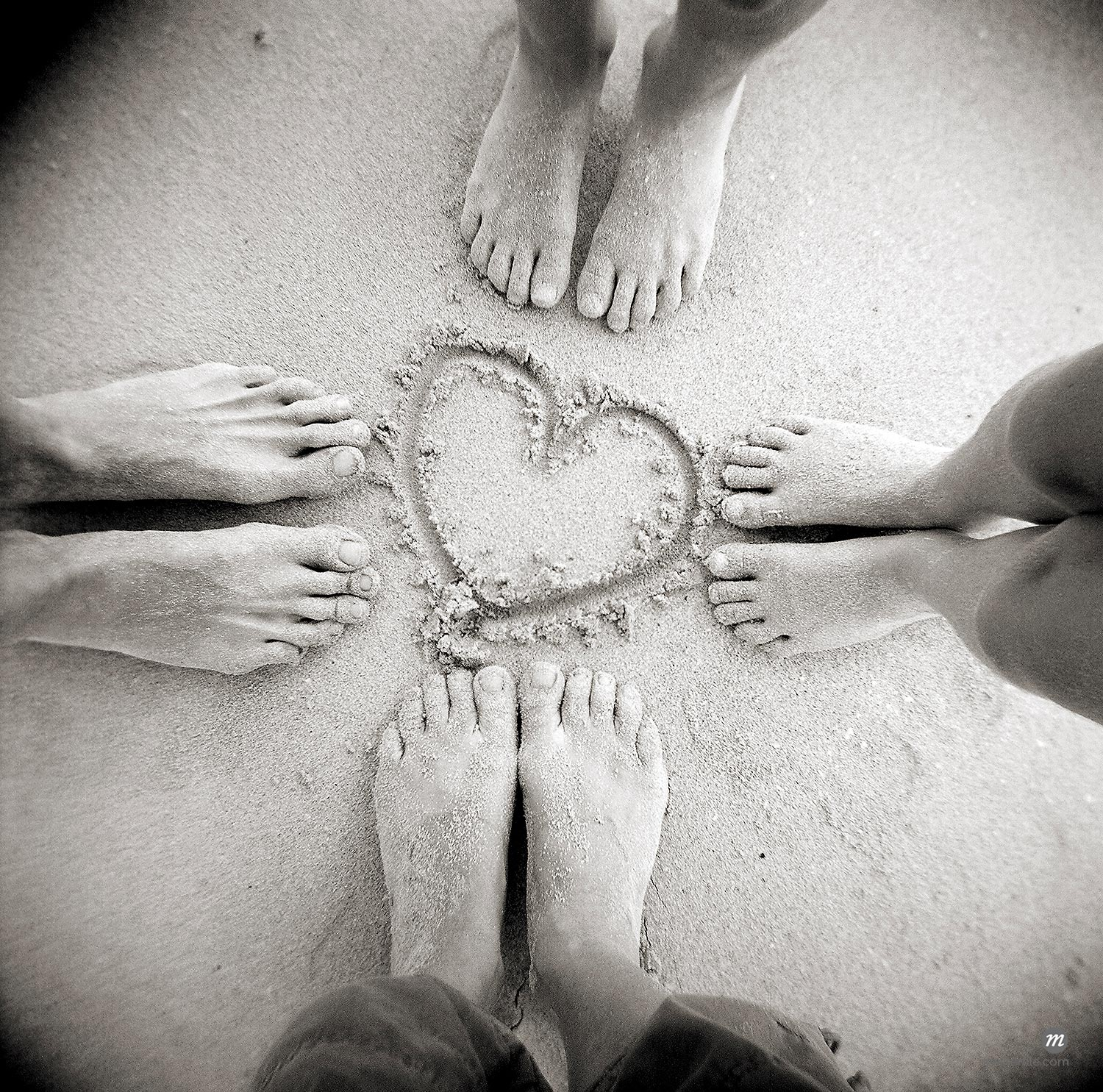 Four pairs of feet standing around heart drawn in sand on beach  © Robert Harding Images / Masterfile