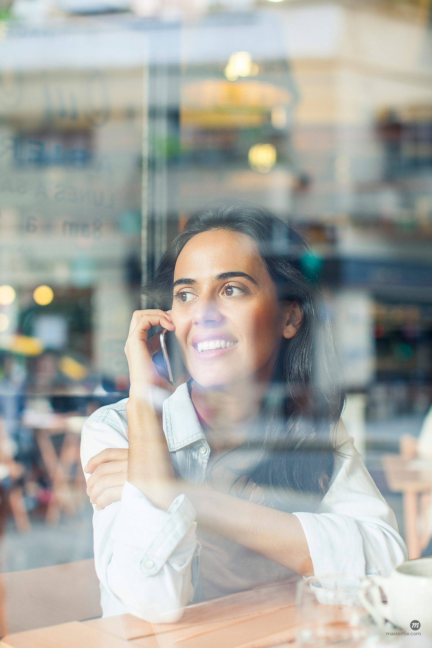 Woman in coffee shop window talking on cellphone  © Masterfile