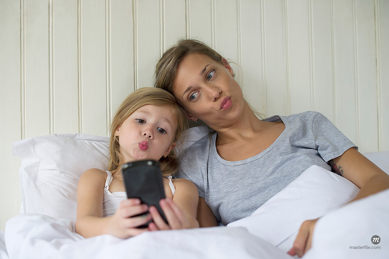 Mother and daughter posing for selfie in bed  © Masterfile