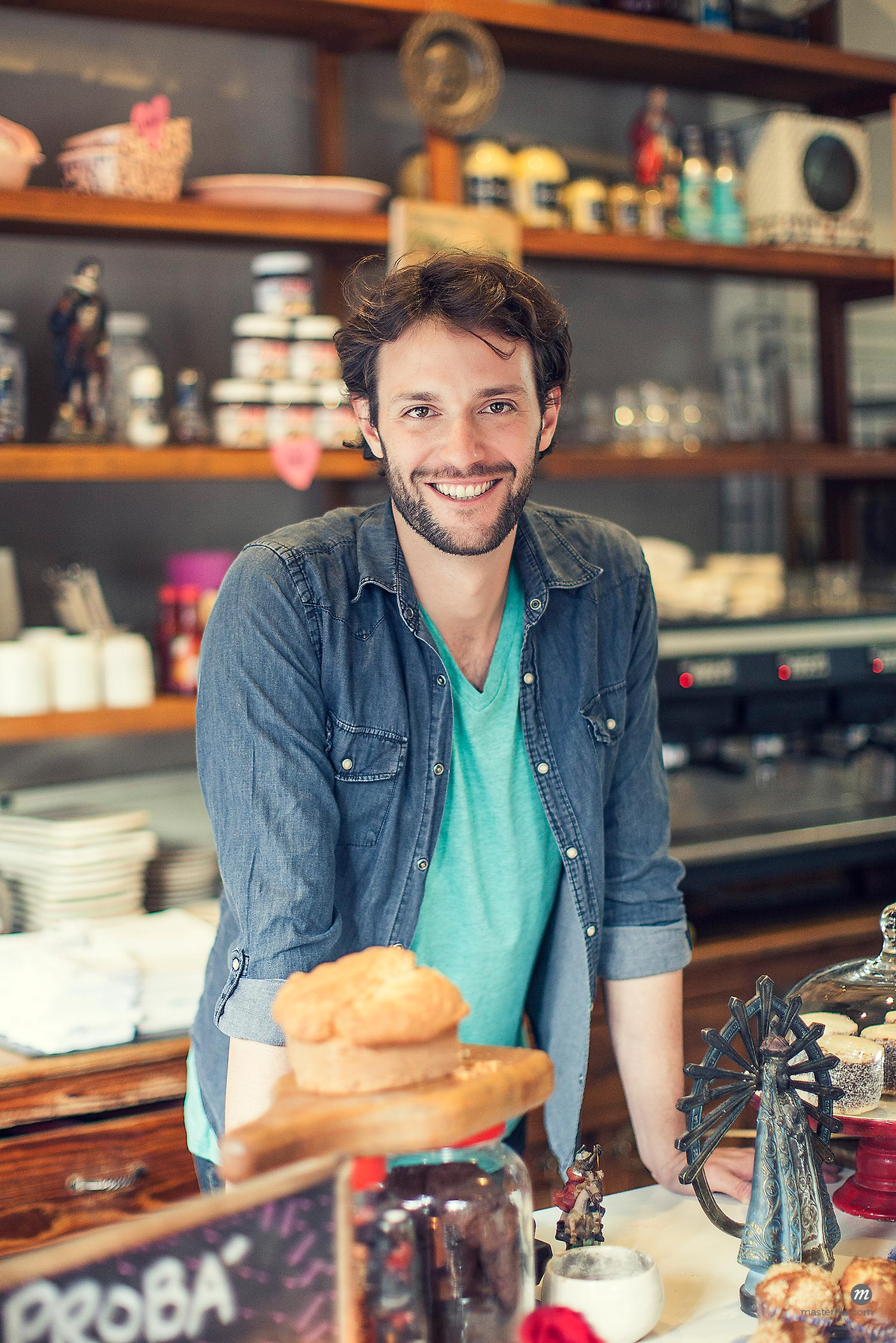 Coffee shop owner standing at counter with baked goods  © Masterfile