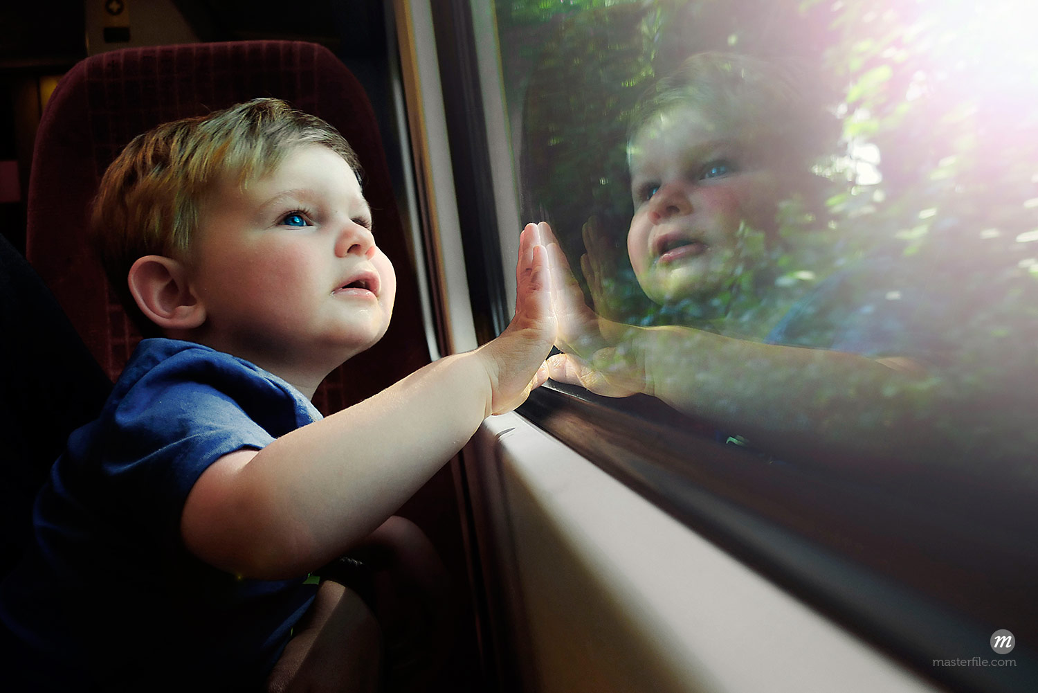 Male toddler gazing out train window in awe  © Masterfile